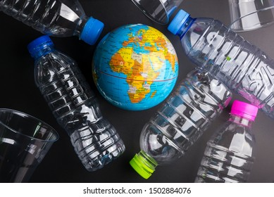 Earth world globe and plastic bottle waste on the black background.Saving the planet Earth from plastic bags concept.Global warming.Plastic waste overflows the world