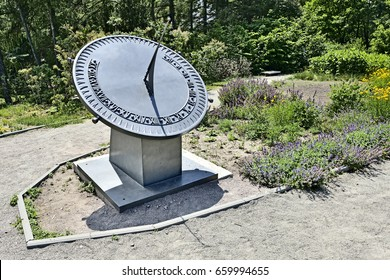 Earth-based sundial with Roman digits on a dial shows time in a sunny day