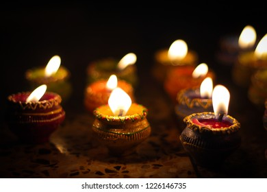 earthen diya lamp lighting with candles on the occasion of diwali and sandhi pujo