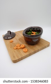 an earthenware pan with vegetables inside,on top of a wooden cutting board,together with its lid and some carrot slices