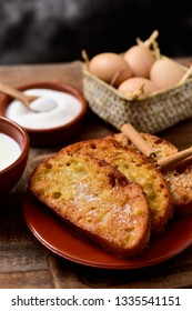 an earthenware plate with some torrijas, typical spanish dessert eaten in Lent and Easter, and some of the ingredients to prepare it, such as eggs, cinnamon or sugar, on a wooden table