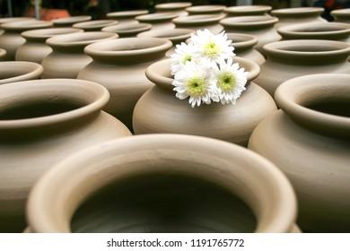 earthenware vintage  handmade carved pots arranged in a pattern of Thai art