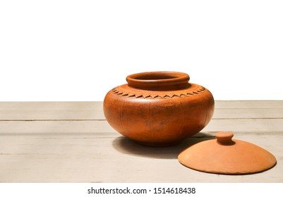 earthenware water pot with ancient patterns on white wooden background