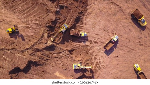Earthmoving equipment. Aerial view of large construction site with several earthmover machines.