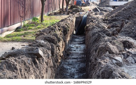 Earthwork. A deep long trench dug in the ground for laying cables, pipes. Telecommunications industry.