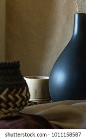 Earthy coloured still life photograph with archaic wooden and ceramic objects