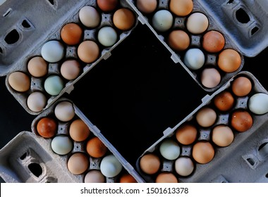 Earthy tones of organic free range farm fresh chicken eggs in cartons, top down view on black background with copy space.