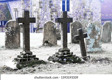 An eary scarey English grave yard with about twenty grave stones, the three headstones in the foreground are in the shape of large Cristian crosses, in the back ground of an ancient English church