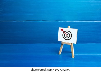 Easel with an arrow in target center. Direct hit, Bulls-eye, straight to the point. Marketing and targeting audience. Complete success. Advertising strategy. Excellent job. Reached goal, best result.