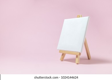 Easel for artists and blank canvas miniature on pastel pink background. Art minimal concept.