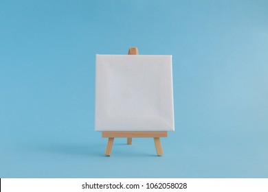 Easel for artists and blank canvas miniature on pastel blue background. Art minimal concept.