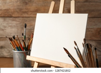 Easel with blank canvas board and brushes on table near wooden wall. Children's painting