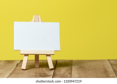 easel with blank canvas isolated on yellow background