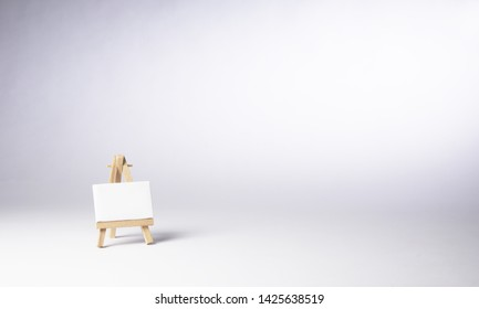 Easel and blank canvas in a white empty void. Copy text space. Shooting in studio. White background.