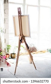 Easel with canvas standing in empty artistic studio
