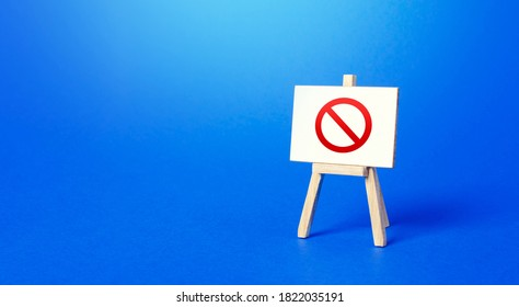 Easel with the prohibition sign NO on a blue background. Restricted area. Restrictions and Sanctions. Out of stock. Ban and Embargo. Failed strategy. Inaccessibility, taboo. Blocking.