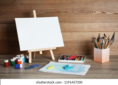 Easel with space for design and set of professional art supplies on table against wooden background