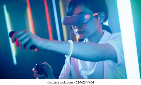 East Asian Pro Gamer Wearing Virtual Reality Headset Plays Online Video Game with Joysticks / Controllers. Cool Retro Red Neon Colors in the Room.