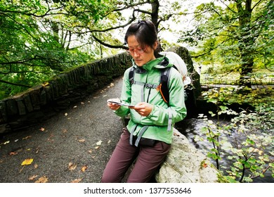 An East Asian Woman, reading a map, hiking in Lake District, Cumbria, UK.