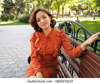 East Asian woman sitting on park bench smiling happy at camera. Pretty young japanese woman enjoying summer in park on parkbench. Copyspace.