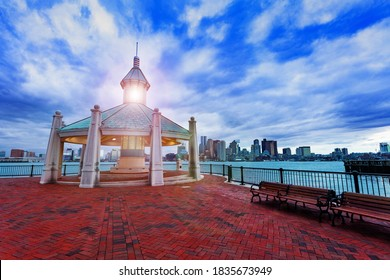 East Boston Piers Park Gazebo with lighthouse light in the evening over downtown panorama view