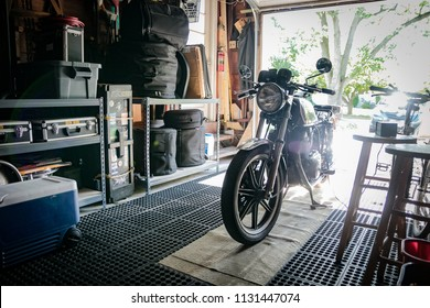 East Brunswick, NJ - July 8, 2018: Sunlight shines into open garage space; with vintage motorcycle and drums/music equipment in storage on shelving.