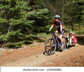 EAST BURKE VERMONT/USA 10 JULY 2018  A lady mountain biker towing her daughter in a Weehoo child bike trailer in the Kingdom Trails at East Burke in Vermont, USA