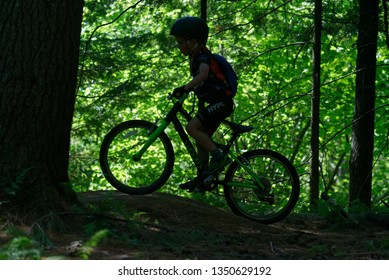 EAST BURKE VT/USA JULY 09 2018 A young boy (6 yrs old) on a mountain bike silhouetted against bright sunlit foliage in East Burke's Kingdom Trails, Vermont, USA