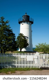 East Chop lighthouse tower with its cast iron tower construction in front of white picket fence on a summer day on Martha's Vineyard island in Massachusetts.