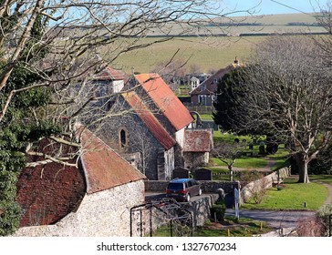 East Dean, East Sussex, England, U.K. - 02/20/2019. Looking down from the hill by the village to the parish church of St. Simon and St Jude. The village is within the South Downs National Park.