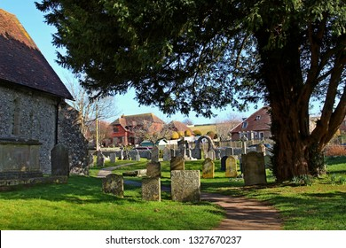 East Dean, East Sussex, England, U.K. - 02/20/2019. The churchyard of St. Simon and St. Jude parish church in the centre of the village. An ancient tree shades the aged gravestones.