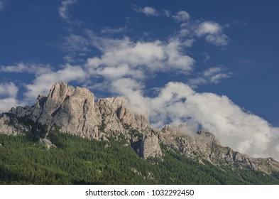 East face of Vallaccia mountain group summits Sas de la Dodesc, Sas de la Undesc and Sass Aut, subgroup of Marmolada group, as seen from Vigo di Fassa village, Dolomites, Italy
