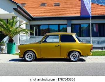 East German made perfectly restored  small two stroke old car in side view parked along concrete sidewalk. bright summer day. popular old car in Europe. European flag and palm tree in the background