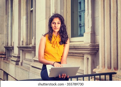 East Indian American Business Woman in New York. Wearing sleeveless orange shirt, a college student sitting by office building, working on laptop computer, thinking. Instagram filtered effect.