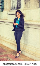 East Indian American student studying in New York, wearing black blazer, blue under shirt, striped pants, heels, standing by wall on street, reading message on cell phone. Instagram filtered look.