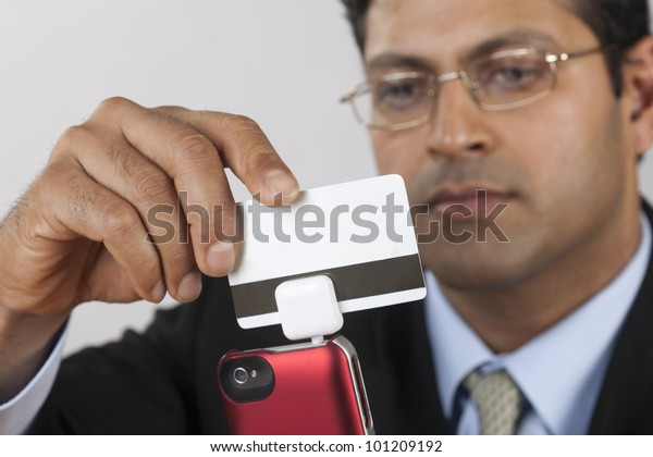 East Indian businessman using a credit card payment swiper on his Smart Phone