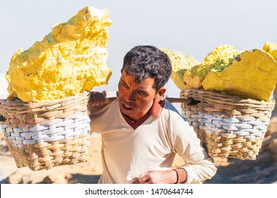 East Java, Indonesia - July 2019 : A sulfur miner working at Kawah Ijen volcano, Indonesia. Who face excruciating heat, toxic fumes, and huge loads in exchange for about five dollars a trip.