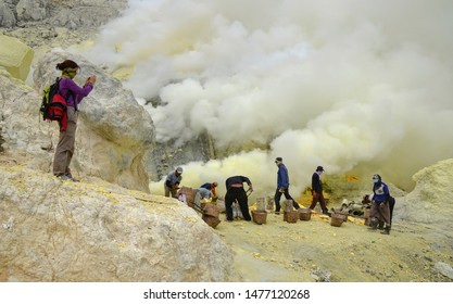 EAST JAVA, INDONESIA - May 18, 2014:  miners extracting sulfur inside the crater of Kawah Ijen volcano, facing excruciating heat, toxic fumes, and huge load.