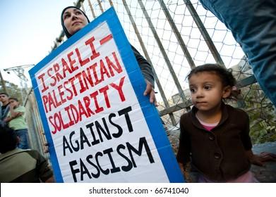 "EAST JERUSALEM - DECEMBER 3: A woman holds a sign reading: ""Israeli-Palestinian Solidarity Agasint Fascism"" among hundreds activists marching in Jerusalem's Al-Issawiya neighborhood on Dec. 3, 2010."