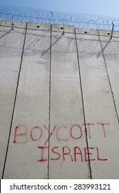 "EAST JERUSALEM, OCCUPIED PALESTINIAN TERRITORIES - MARCH 26: Graffiti on the Israeli separation wall dividing the East Jerusalem neighborhood of Abu Dis reads, ""Boycott Israel"", March 26, 2012."
