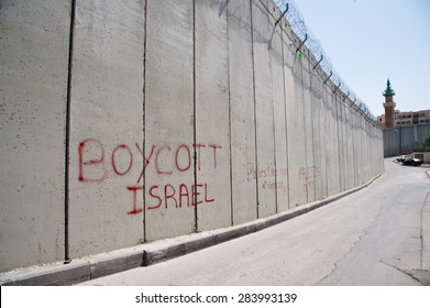 "EAST JERUSALEM, OCCUPIED PALESTINIAN TERRITORIES - MARCH 26: Graffiti on the Israeli separation wall dividing the East Jerusalem neighborhood of Abu Dis reads, ""Boycott Israel"", March 26, 2012."