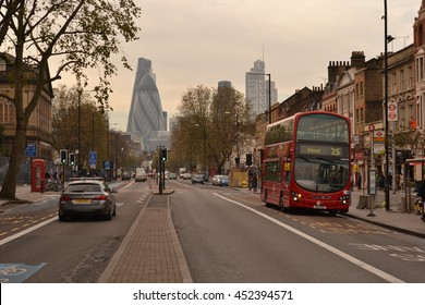 East London November 2014; Red double decker bus on Whitechapel Road and skyscraper Gherkin in the distance .