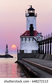 The East Pierhead Light in Michigan City, Indiana with a sailboat on the horizon and setting sun.