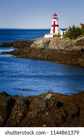 East Quoddy Head lighthouse, referred also as head Harbor light, is situated on the rocky Canadian shore of Campobello Island, during low tide.