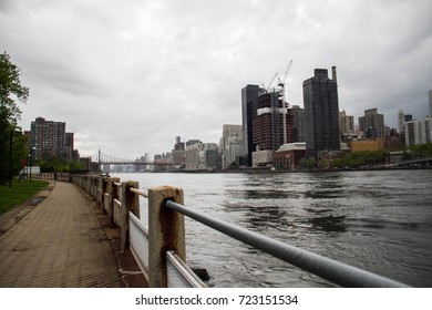 East river between Manhattan and Roosevelt island with cloudy sky