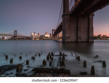 East river view at sunrise from broken pier with to bridges Manhattan and Brooklyn