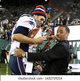 EAST RUTHERFORD, NJ - NOV 22: New England Patriots quarterback Tom Brady (12) hands a turkey leg to NBC analyst Rodney Harrison after the game against the New York Jets on November 22, 2012.