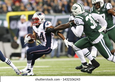 EAST RUTHERFORD, NJ-NOV 22: New York Jets linebacker David Harris (52) and safety LaRon Landry (30) tackle New England Patriots running back Shane Vereen (34) at MetLife Stadium on November 22, 2019.