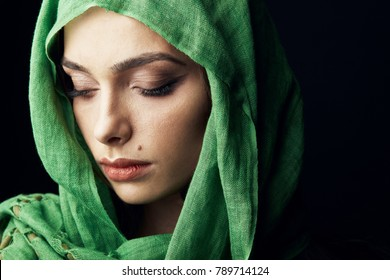 East style close-up studio portrait of attractive woman with big lips and birthmark near lips, wearing green hijab and looking down