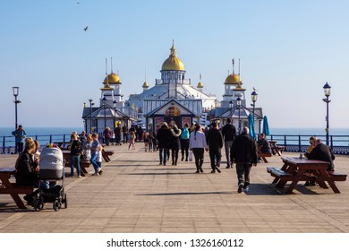 East Sussex, UK - February 23rd 2019: Tourists walking along the historic Eastbourne Pier in the seaside town of Eastbourne in East Sussex, UK.